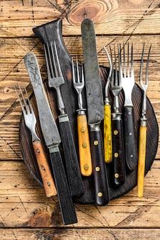 カトラリーナイフとフォークの素朴なセット。木製のテーブル。上面図。