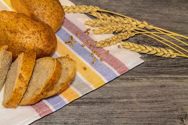 木製のテーブルの上にパンのパン、穀物、小麦の穂のある素朴な静物