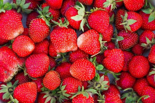 素朴なイチゴの新鮮な有機ベリーマクロ赤い背景