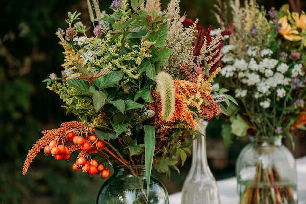 Rustic style bouquets on the table in glass vases and jars