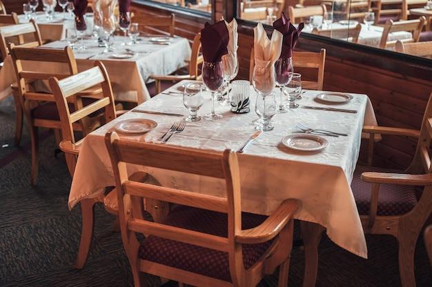 레스토랑에서 식기, 유리 제품, 네이퍼리가 있는 소박한 스타일의 나무 식탁