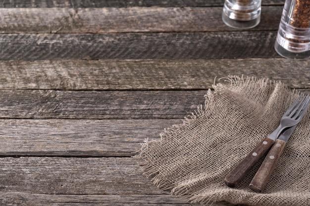フォーク、ナイフ、キャンディーと素朴なスタイルの木製の背景。テキストスペース