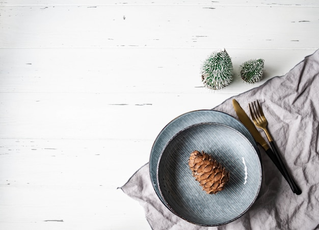 Rustic table setting for christmas or new year. blue plates, grey napkin, pine cone and appliances on white wood table. top view. copy space