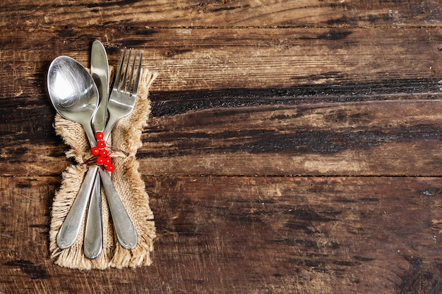 세인트 발렌타인의 저녁 식사를위한 소박한 테이블 설정입니다. 자루 냅킨, 수저 및 축제 장식. 빈티지 나무 보드 배경, 평면도