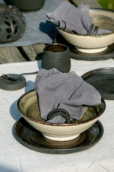 Rustic table setting outside in garden with empty craft ceramic tableware, black plates and rough bowls, pumpkin decorations, on linen tablecloth over old wooden table. garden party. close up