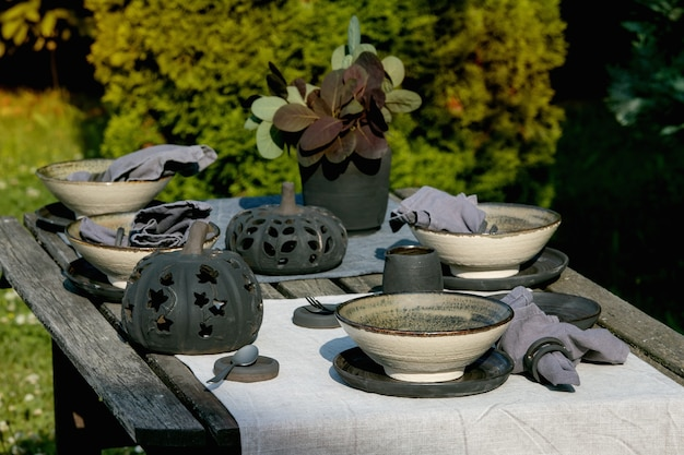Rustic table setting outside in garden with empty craft ceramic tableware, black plates and rough bowls, pumpkin decorations, on linen tablecloth over old wooden table. garden party