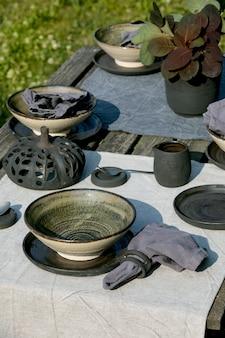 오래된 나무 테이블 위에 린넨 식탁보에 빈 공예 세라믹 식기, 검은 접시, 거친 그릇, 호박 장식이 있는 정원 외부의 소박한 테이블. 정원 파티