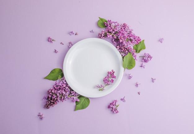 ライトテーブルのロマンチックなディナーにライラックの花と素朴なテーブルの設定