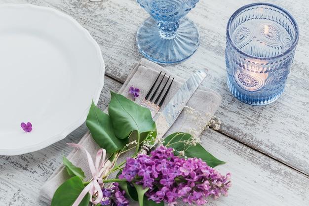 明るい木製のテーブルにライラックの花と素朴なテーブルの設定