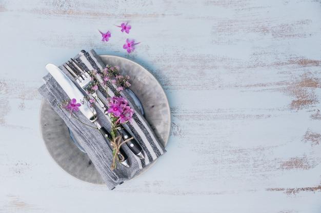 明るい木製のテーブルにピンクの花と素朴なテーブルの設定。プロヴァンススタイルの休日の装飾。ロマンチックなディナー。テキスト用のコピースペースのある上面図