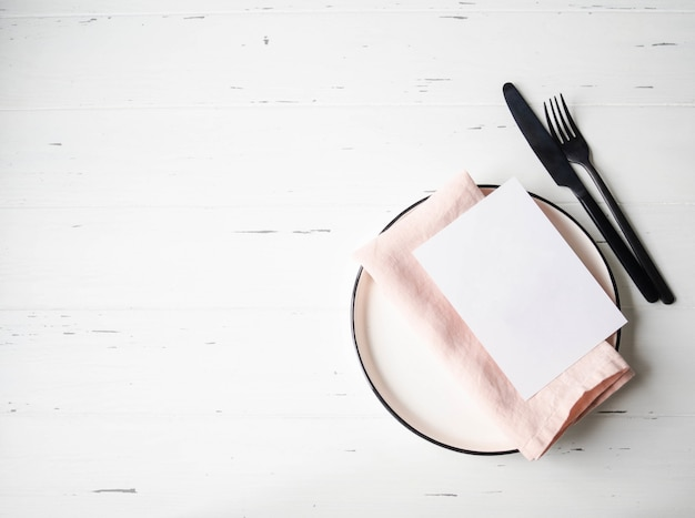 Rustic table setting with plate, pink napkin, card and appliances on white wood table. top view.