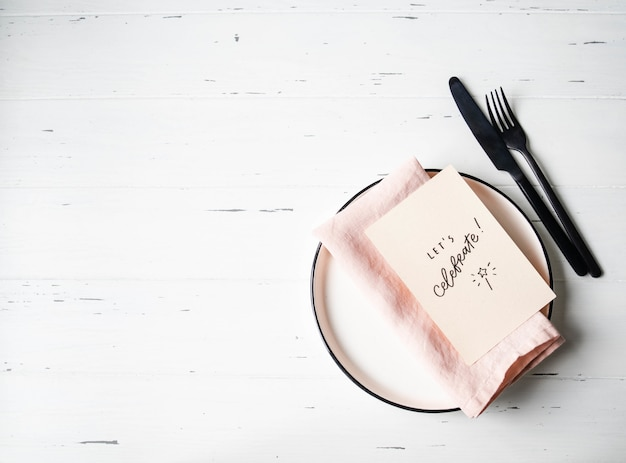 Rustic table setting with plate, pink napkin, gritting card and appliances on white wood table. top view.