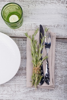 Rustic table setting with rosemary on light wooden table. holidays decoration on provence style. romantic dinner. top view