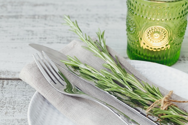 Rustic table setting with rosemary on light wooden table. holidays decoration on provence style. romantic dinner.