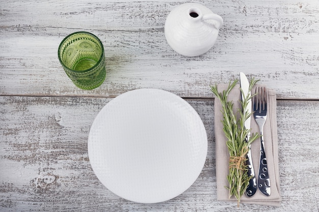 Rustic table setting with rosemary on light wooden table with copyspace. holidays decoration on provence style. romantic dinner. top view