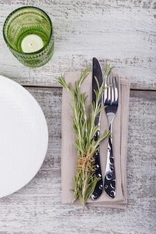 明るい木製のテーブルにローズマリーと素朴なテーブルセッティング。プロヴァンススタイルの休日の装飾。ロマンチックなディナー。上面図