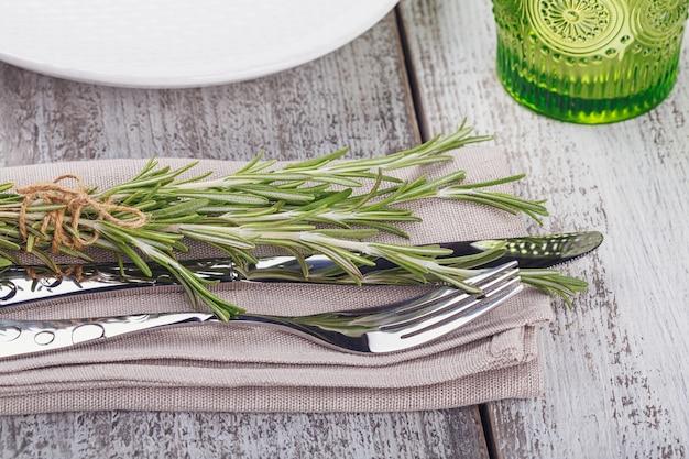明るい木製のテーブルにローズマリーと素朴なテーブルセッティング。プロヴァンススタイルの休日の装飾。ロマンチックなディナー。