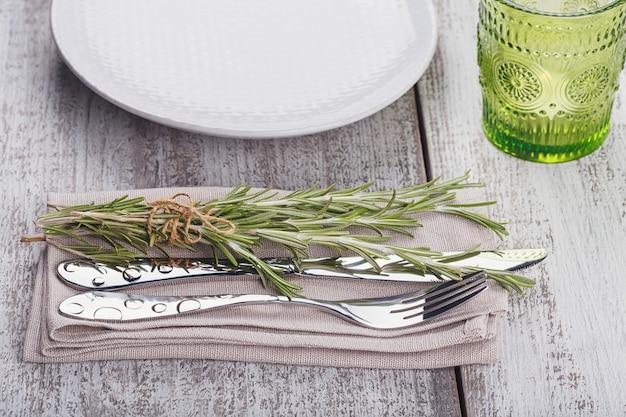 コピースペース付きの明るい木製のテーブルにローズマリーの素朴なテーブルセッティング。プロヴァンススタイルの休日の装飾。ロマンチックなディナー。