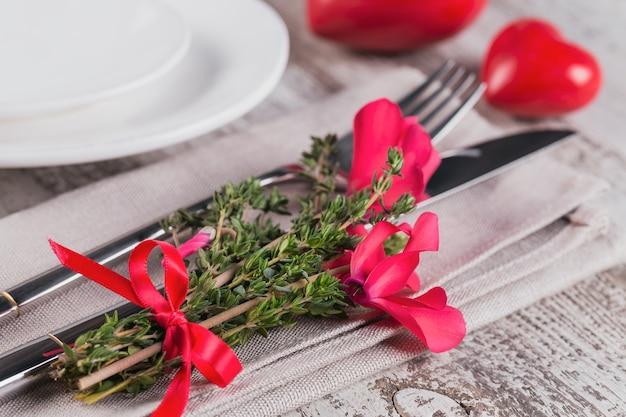 Сервировка стола в деревенском стиле с цветами тимьяна и цикламена и украшением в форме сердца на светлом деревянном столе с copyspace