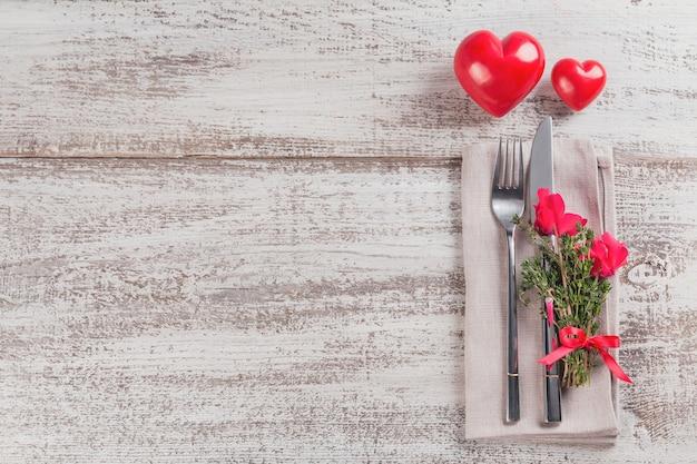 Сервировка стола в деревенском стиле с цветами тимьяна и цикламена и украшение в форме сердца на светлом деревянном столе