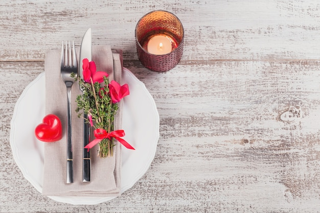 Rustic table setting with thyme and cyclamen flowers and shape of heart decoration on light wooden table with copyspace