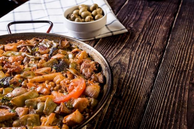 Стол в деревенском стиле с паэльей и зелеными оливками. вкусная традиционная еда, вкусы мира