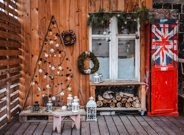 Терраса в деревенском стиле украшена к рождеству натуральными материалами