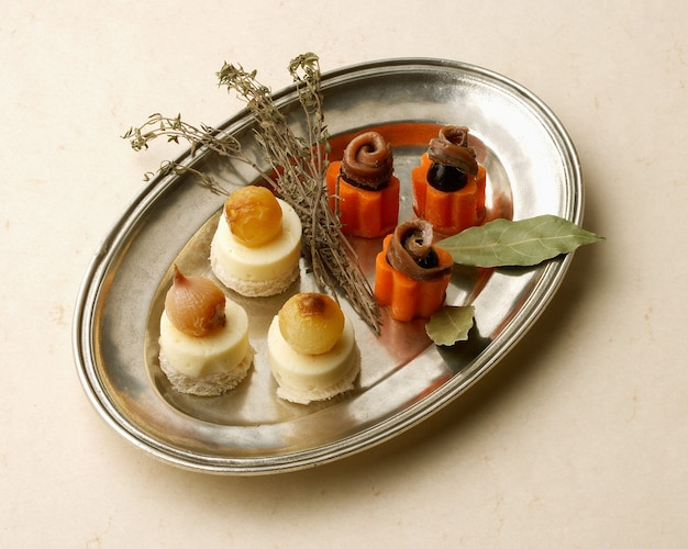 Rustic tray with anchovies and cheese canapes