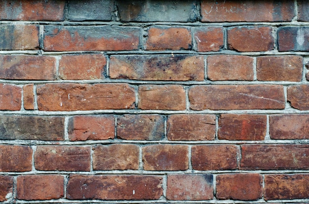 Rustic vintage bakcground of red brick wall cladding with cement seams