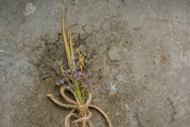 Rustic vintage buttonhole bouquet of lavender on rough concrete