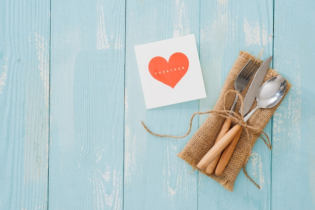 Rustic vintage set of cutlery knife, spoon, fork. blue background. top view