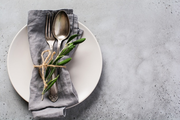 Rustic vintage set of cutlery. plate with grey linen napkin, fork and spoon, olive tree branch over rustic concrete gray old. fall holiday table decoration setting.