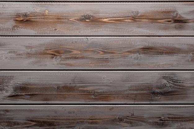 Деревенский выветрившийся серый и коричневый деревянный фон с сучками и отверстиями для ногтей