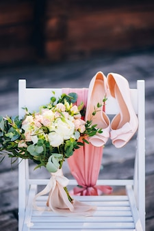 Rustic wedding bouquet and delicate bridal shoes on a white chair.