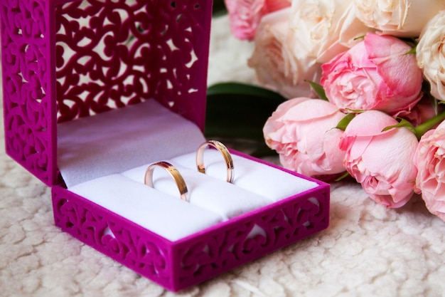 Rustic wedding bouquet and rings in the box on a luxury sofa