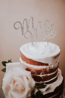 Rustic wedding cake with mr and mrs topper on brown texture background