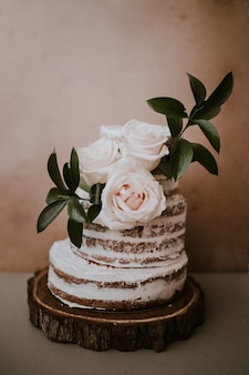 Rustic wedding cake with three white roses topper on brown texture background