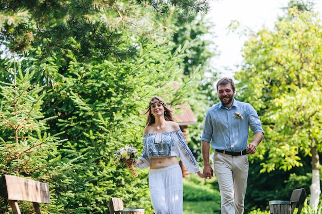 Rustic wedding couple of gorgeous bride and stylish groom holding hand in hand and rushes somewhere