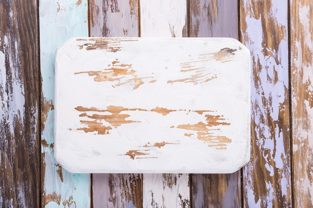 Rustic white cutting board on multicolored old wooden plank background. copy space.