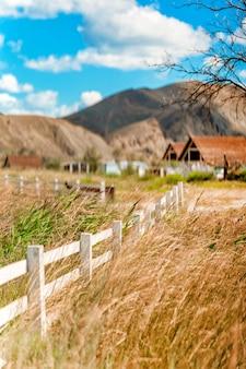 Деревенский белый забор и прекрасный вид на холмы и горы
