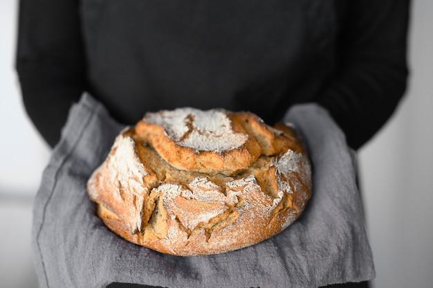 Деревенский цельнозерновой хлеб на закваске, руки держат свежий хлеб