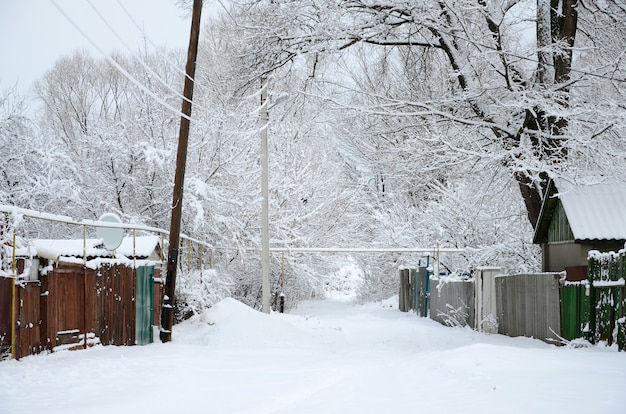 A rustic winter landscape with some old houses and a broad highway covered with a thick layer of snow