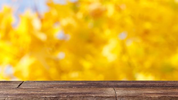 黄色のボケ味の抽象的な背景に素朴な木製のテーブル。
