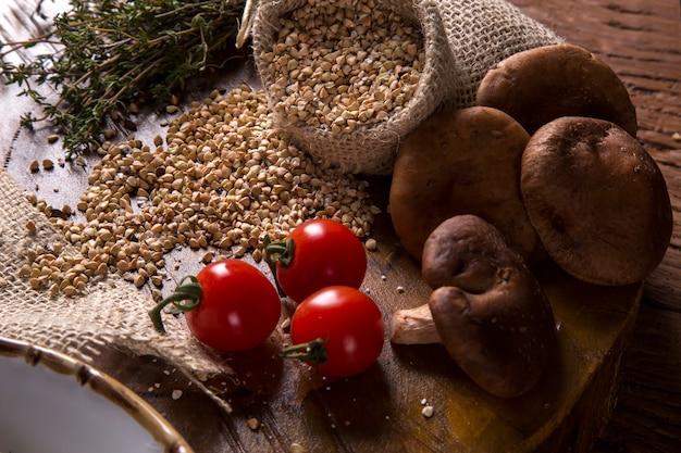新鮮な小麦、キノコ、トマトの素朴な木