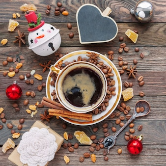 Rustic wooden background with cup of coffee and new year decorations