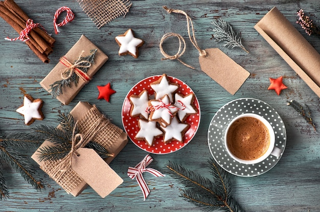 Rustic wooden background with cup of hot coffee and gifts
