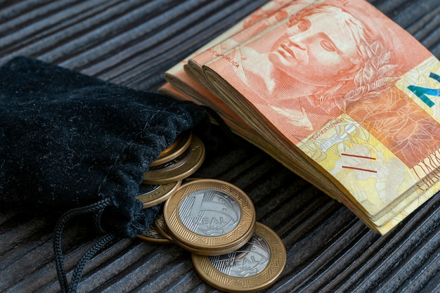 お金のスタックとブラジルのコインと財布と素朴な木製の背景。経済概念