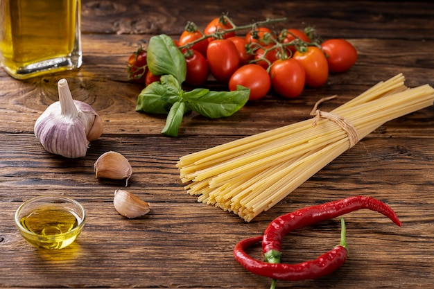 Rustic wooden board with raw ingredients to season pasta in italian way