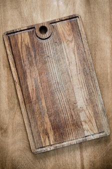 Rustic wooden cutting board on wooden background.