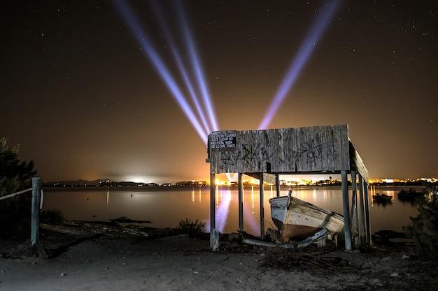 밤에 불이 켜진 마을에서 수평선에 가벼운 대포가있는 소박한 목조 부두